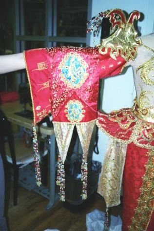 The sleeve embroidery is a combination of purchased fusible appliqués and custom machine work while the epaulette is gold-leafed paper mache.