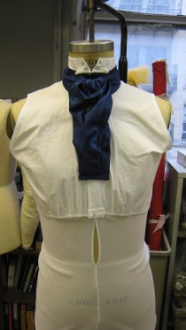 Mr. Bates' shirt is sleeveless to reduce bulk and is attached to a powernet base to hold in place beneath the vest. The sleeve cuffs are faked into the coat.