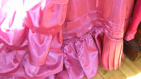 A typical tucked Victorian petticoat with gathered and pleated ruffles supports the skirt of the costume.