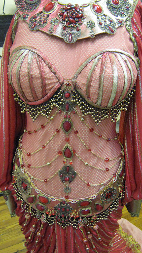The dress features a boned bodice overlaid in red fishnet with beaded swags and operatic scale jewelry.