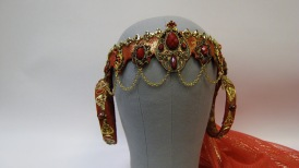 Delilah's headpiece is made from leather covered plastic with chain swags and findings with a metallic chiffon veil.