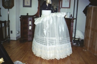 Wheel farthingale plate made of plastic sheeting reinforced with polyethylene tubing, covered with a detachable poly organza petticoat