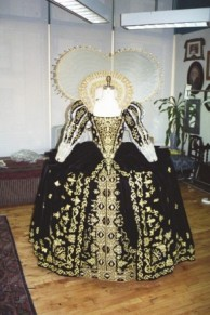 The skirt is tucked up onto a fabric stay to hold the row of pleats at the edge of the wheel of the farthingale